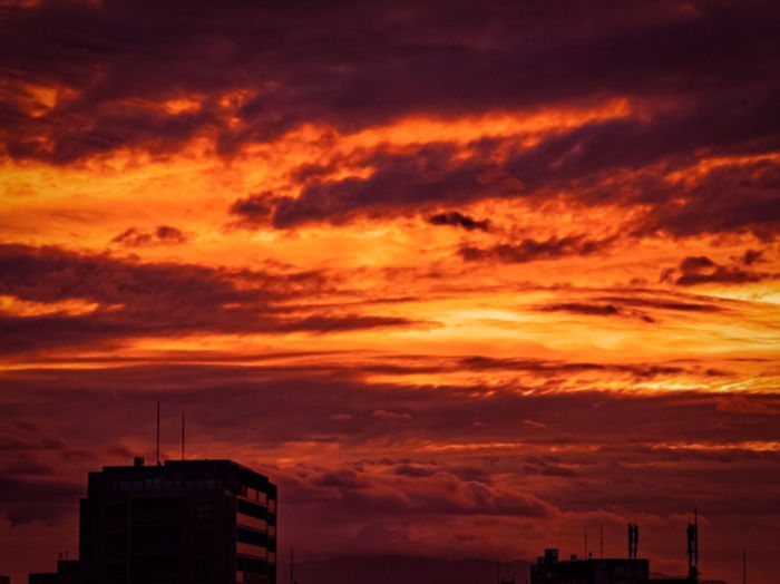 Low angle view of silhouette buildings against dramatic sky during sunset