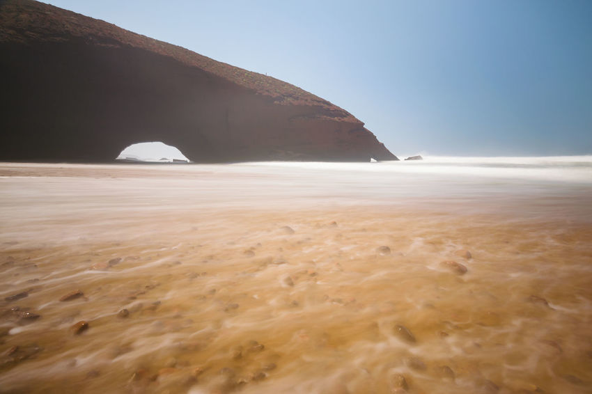Long exposure of the Red arches and rocky beach at the Atlantic Ocean in the region Sous-Massa-Draa, Sidi Ifni, Legzira, Morocco, Africa. Atlantic Ocean Beautiful Legzira Morocco Ochre Red Sea Spray Sidi Ifni Africa Arch Beach Beauty In Nature Clear Sky Coast Foam Landscape Limestone Long Exposure Ocean Sand Tranquility Travel Destinations