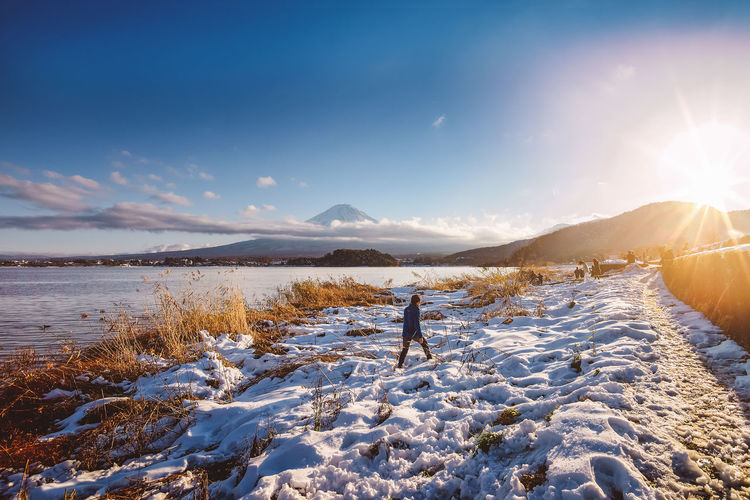 One of the best views of Mount Fuji can be enjoyed from Lake Kawaguchiko. It is accessible through a sightseeing retro bus from Kawaguchiko train station then you can drop off anywhere up to bus stop 22. Japan The Traveler - 2018 EyeEm Awards Beauty In Nature Cold Temperature Fuji Land Leisure Activity Lens Flare Lifestyles Mountain Mountain Range Nature Non-urban Scene One Person Outdoors Real People Scenics - Nature Sky Snow Snowcapped Mountain Sun Sunlight Tranquil Scene Tranquility Winter Autumn Mood Human Connection It's About The Journey Moments Of Happiness Capture Tomorrow EyeEmNewHere My Best Photo 17.62°