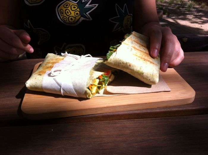 Midsection of person holding wrap sandwich on serving board