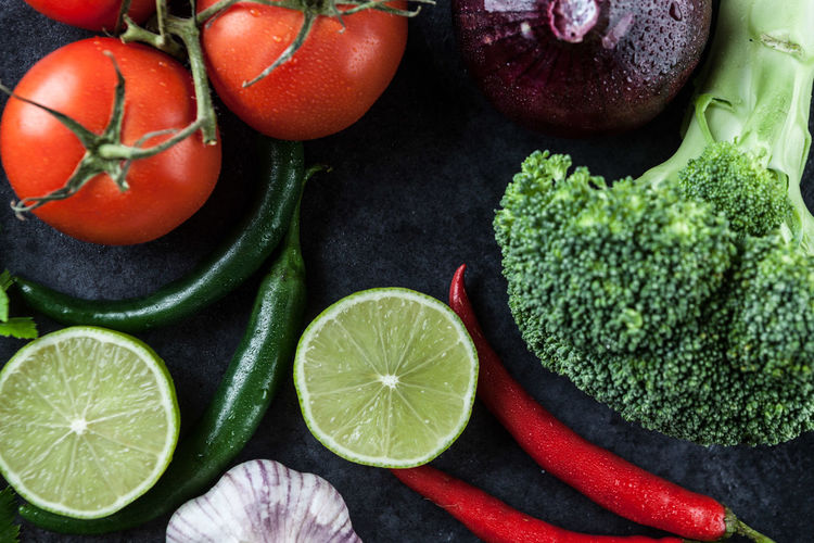 Tomatoes, hot chili peppers, garlic, onion, lime, and broccoli on grunge background. Top view. Vegetarian Food Broccoli Chili  Close-up Day Food Food And Drink Freshness Green Color Healthy Eating High Angle View Indoors  Lime No People Ready-to-eat Tomatoes Top View Vegan Food Vegetable