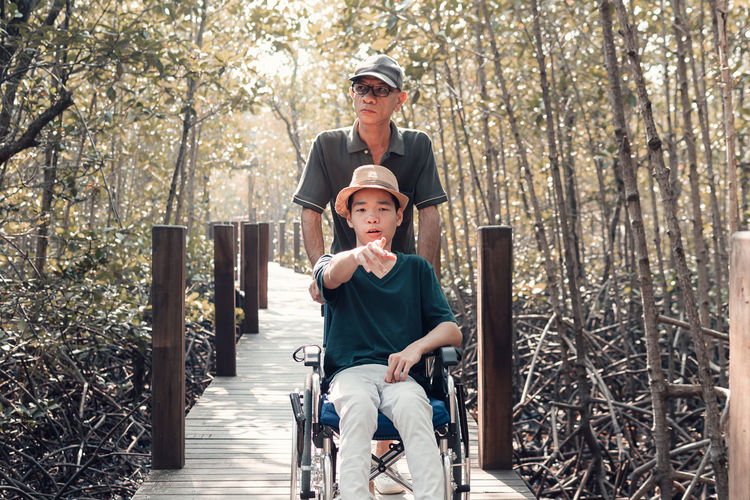 Father with disabled boy on wheelchair against trees