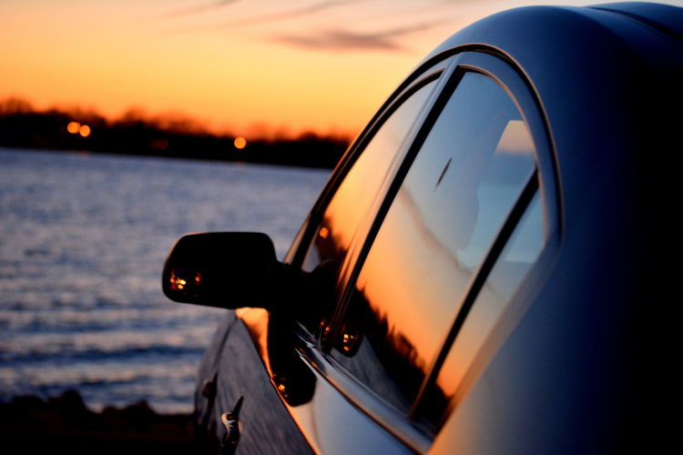 Car Parked Against River At Sunset