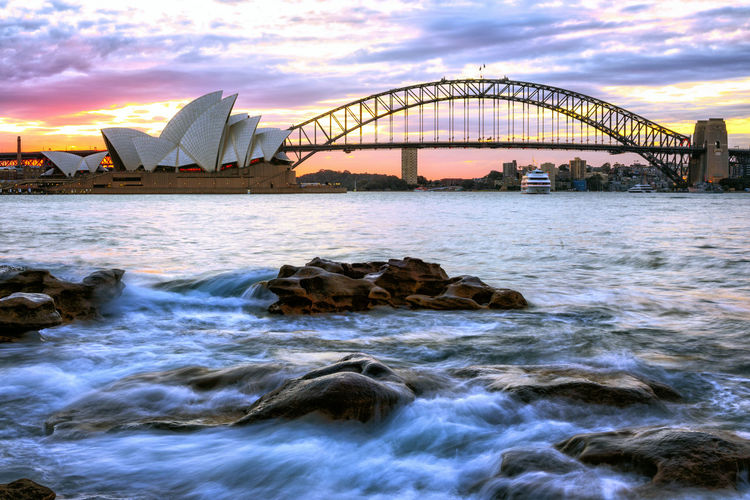 Sydney Opera House By Bridge Over River During Sunset