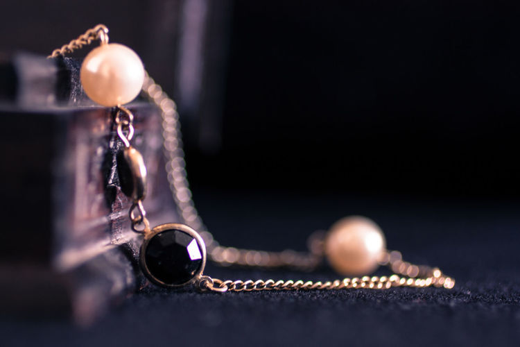 Close-up of necklace against black background