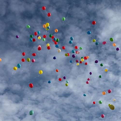 Low angle view of colorful balloons flying against cloudy sky