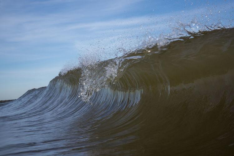 Close-up of sea waves splashing on shore against sky
