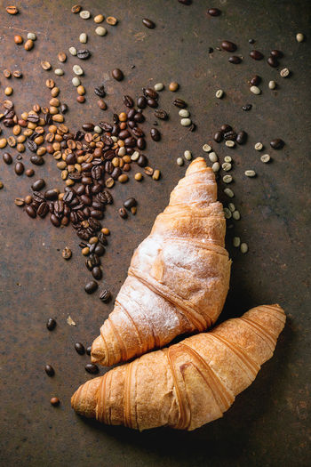 Two fresh baked croissants with heap od roasted and unroasted coffee beans over rusty metal background Baked Bread Breakfast Brown Coffee Coffee Beans Croissant Dark Background Dessert Food And Drink Food Photography Fresh Baked Meal Metal Metal Industry Pastry Rusty Sandwiches Snack Sugar Powder Sweet Food Top View Of Food Two