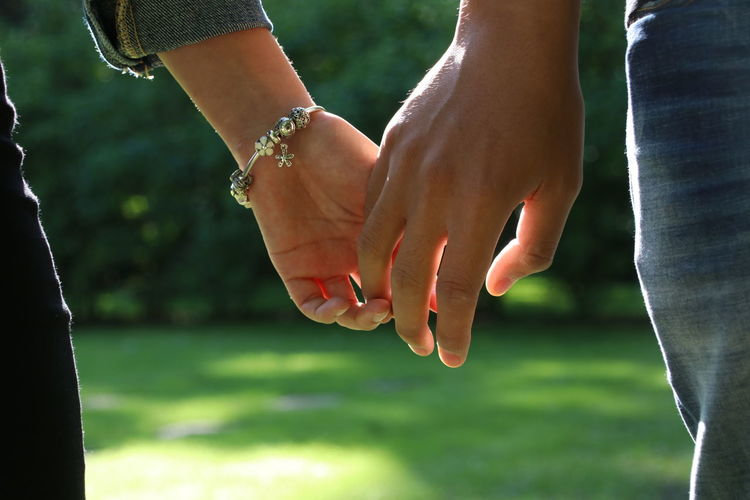 Cropped image of couple holding hands on grass
