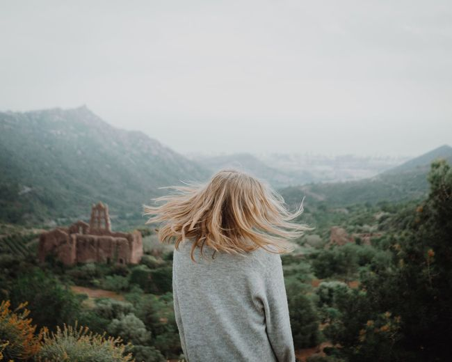 Rear view of woman tossing hair while looking at mountains against sky