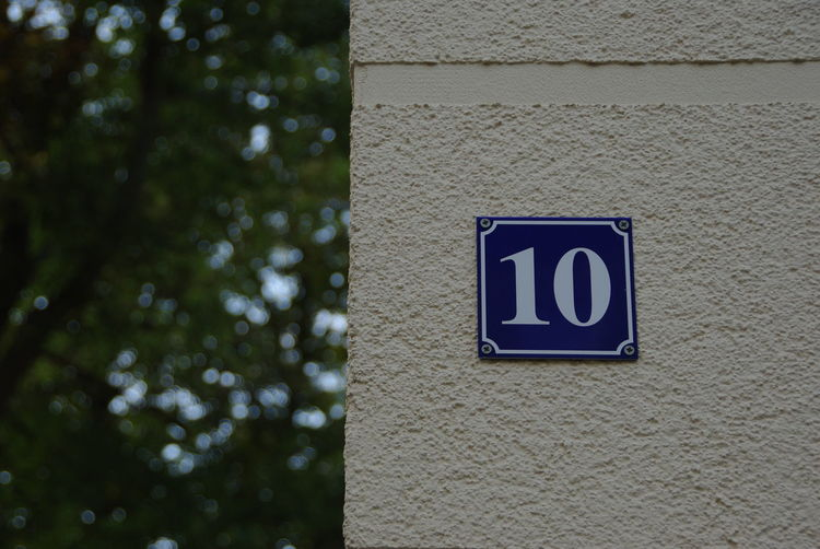 House number 10 Number Plate House Number On Wall House Number Plate No People Sign Focus On Foreground Close-up Blue Outdoors Low Angle View Information Built Structure Western Script Text Wall Day Number Tree Building Exterior Wall Structure