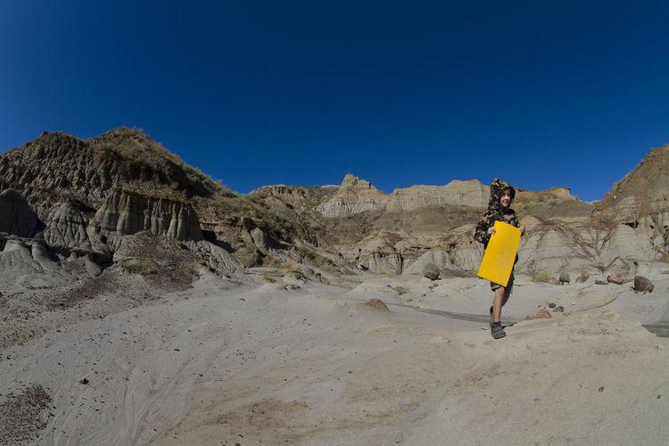 Boy walking on rock against clear blue sky