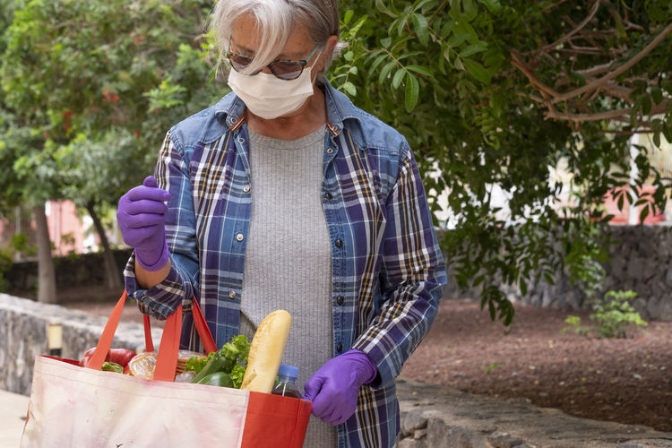 Senior woman holding groceries bag standing by plants