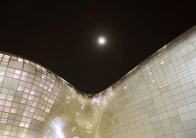 Modern architecture of Dongdaemun Design Plaza at night. The building designed by Zaha Hadid. Architecture Curve Darkness Korea Modern Moon Seoul Zaha Hadid Architects Building Contemporary Design Dongdaemun Design Plaza Famous Place Night Sky Zaha Hadid