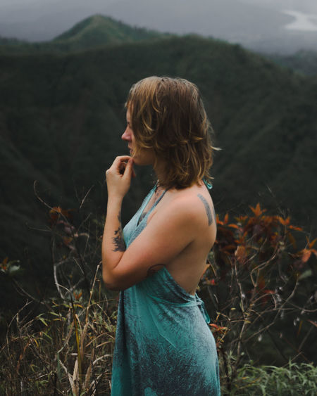 Side view of woman standing against mountain