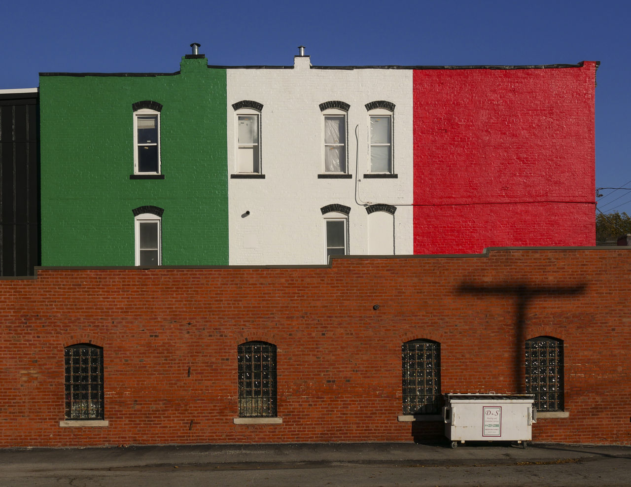 Italian flag paint on building against clear sky