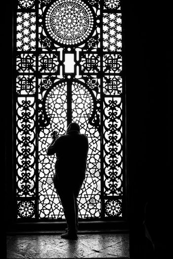 Rear view of silhouette woman standing against glass window