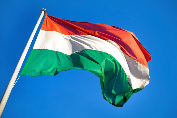 Low angle view of hungarian flag against clear blue sky