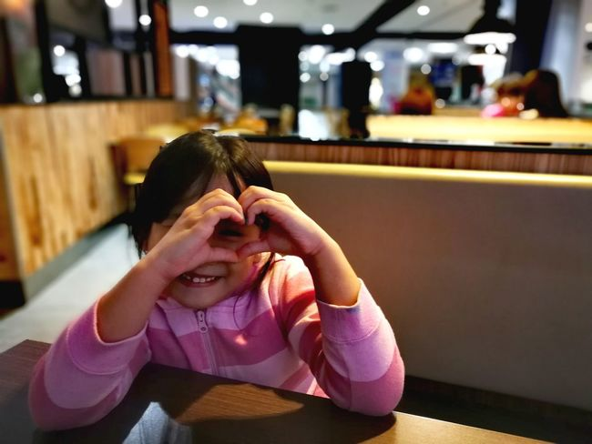 Little girl making heart love sign while smiling happily. Happy Happy People Jovial Sitting Asian Girl Asian Kid Cute Day Hand Gestures Human Hand Indoors  Little Little Girl Love Sign One Person Real People Young Adult Young Woman Young Women