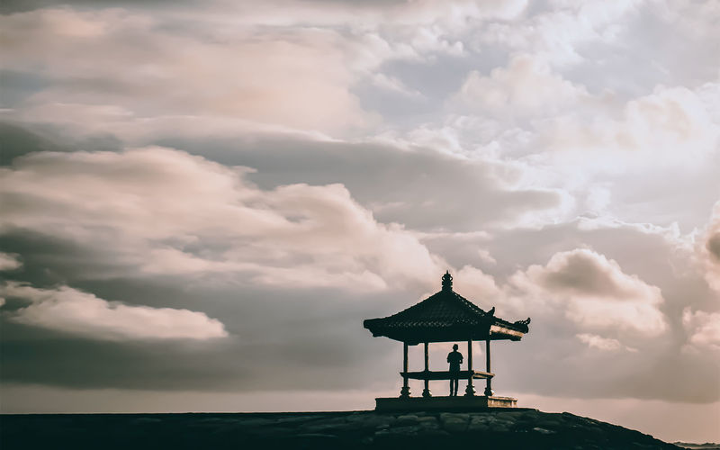 Silhouette person standing in gazebo against cloudy sky