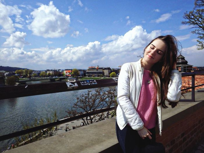 Beautiful Young Woman Standing By River Against Sky In City
