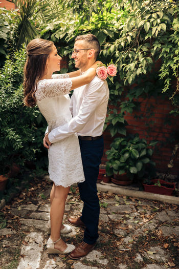 Side view of couple embracing while standing against plants