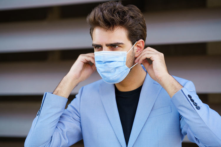 Close-up of young businessman wearing mask looking away while standing outdoors