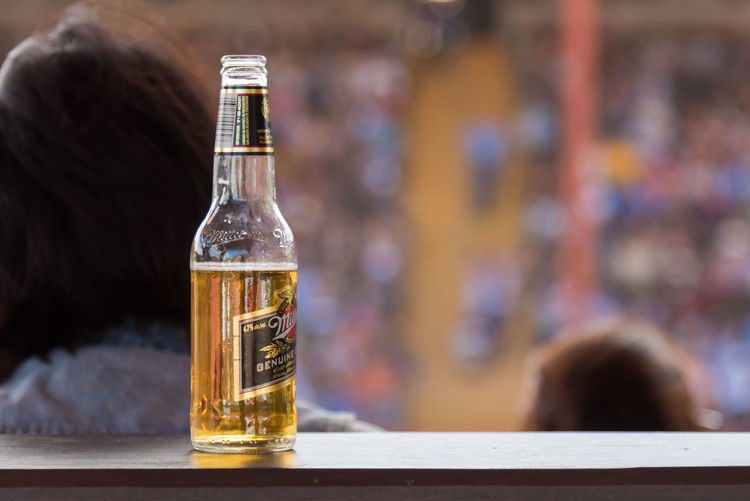 Williams Lake, British Columbia/Canada - July 2, 2016: bottle of beer rests on a ledge in the VIP stands with audience in the background, at the internationally famous 90th Williams Lake Stampede 90th Williams Lake Stampede Beer Beverage Event July Rodeo Spectators VIP Section VIP Stands Alcohol Audience Bottle Close-up Crowd Focus On Foreground Food And Drink Opened Beer Bottle Outdoors People Professional Rodeo Selective Focus Stampede Stampede Grounds Stands Summer