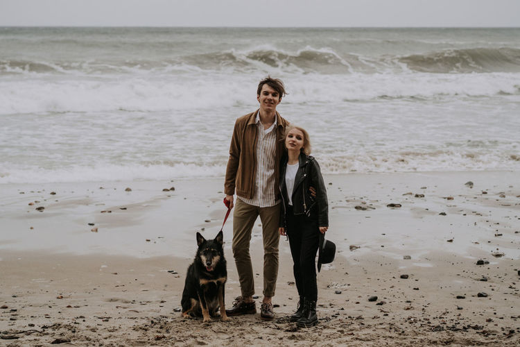 Young attractive couple having fun at he beach with a dog
