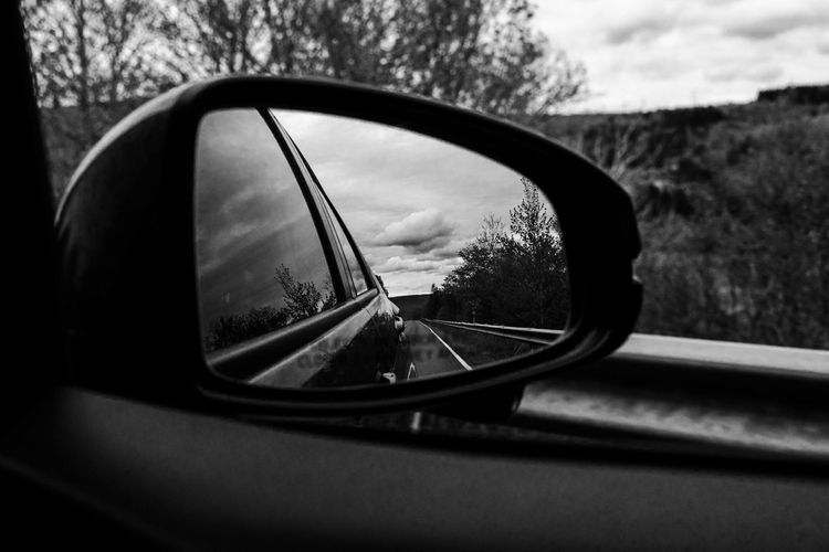 Looking in the side view mirror while driving on a coastal highway. Black And White Car Car Interior Close-up Day Glass - Material Land Vehicle Mirror Mode Of Transportation Motor Vehicle Nature No People Outdoors Personal Accessory Rear-view Mirror Reflection Road Road Trip Side-view Mirror Sky Transportation Travel Tree Vehicle Interior Vehicle Mirror