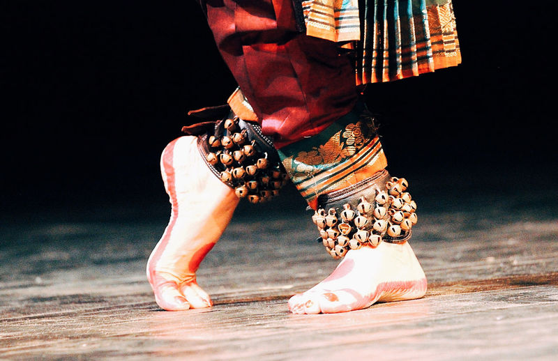 Low section of woman wearing anklet bells performing bharatanatyam dance