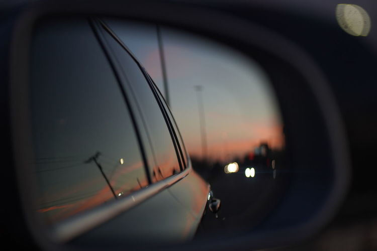 Close-up of side-view mirror at sunset