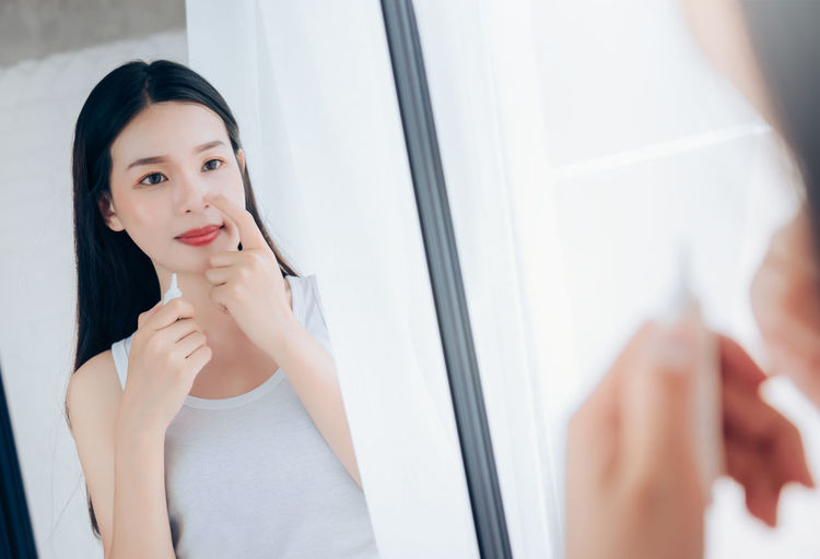Beauty Asian Woman use Acne Gel Skincare after Cleansing on Face His Happiness and Look at mirror in White Bedroom. Young Adult One Person Indoors  Beautiful Woman Beauty Adult Reflection Portrait Women Young Women Mirror Front View Waist Up Hair Lifestyles Preparation  Standing Looking At Camera Hairstyle Contemplation