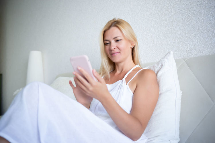 Young woman using mobile phone while sitting on bed