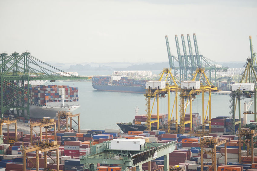 A photo of a sea port with anchored ships, gantry cranes and containers. This is one of the ports of Singapore, the world's busiest! Background Built Structure Business Commercial Dock Commerical Containers Cranes Day Development Dock Harbor Harbour Maritime No People Ocean Outdoors Port Sea Ships Sky Trade Trading Transportation Vessel Water