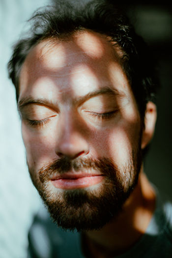 Close-Up Of Eyes Closed Mid Adult Man With Shadow On Face