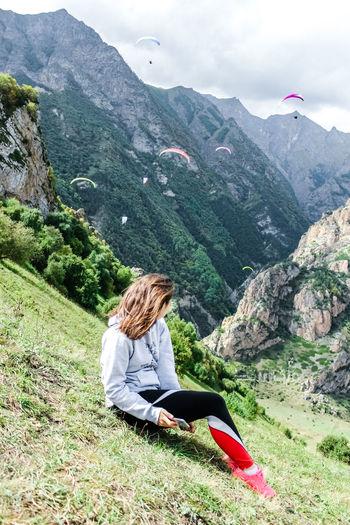 Woman sitting on grassy mountain