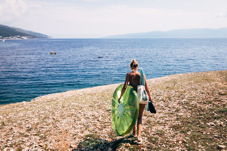 Rear view of woman with pool raft walking at beach