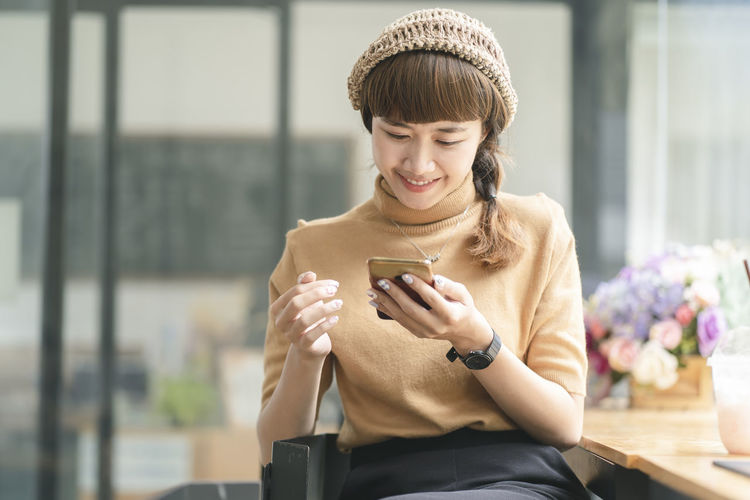Young woman using mobile phone at camera