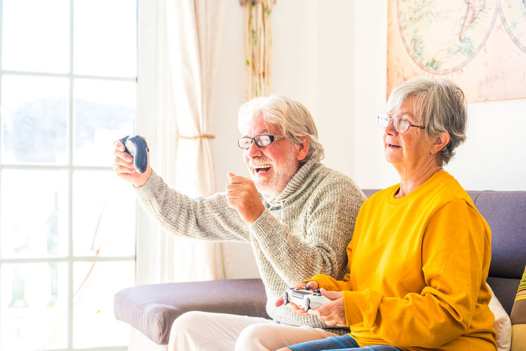 Senior couple playing video game at home