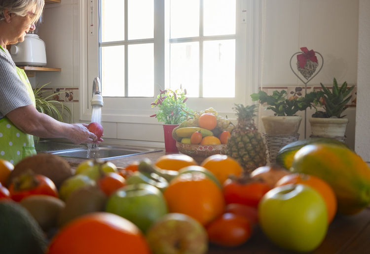 Side view of woman cleaning fruits in kitchen sink