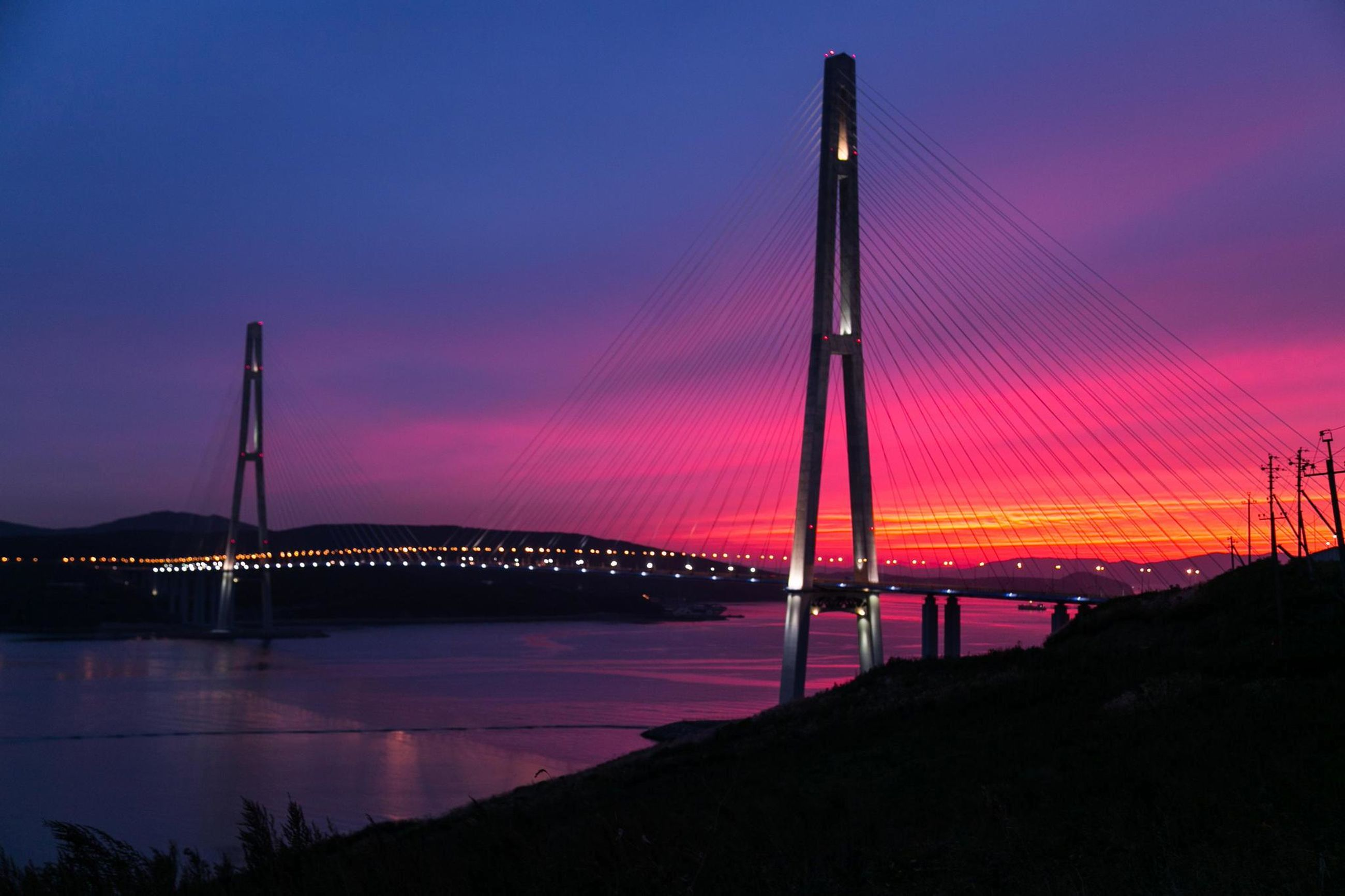 sunset, sky, silhouette, orange color, connection, scenics, tranquility, dusk, tranquil scene, beauty in nature, suspension bridge, bridge - man made structure, illuminated, cloud - sky, nature, idyllic, outdoors, transportation, no people, engineering