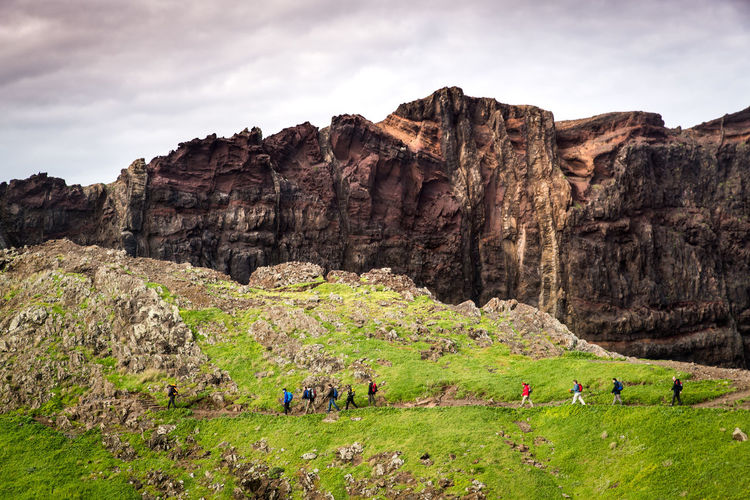 Hikers walking on hill against rocky mountain