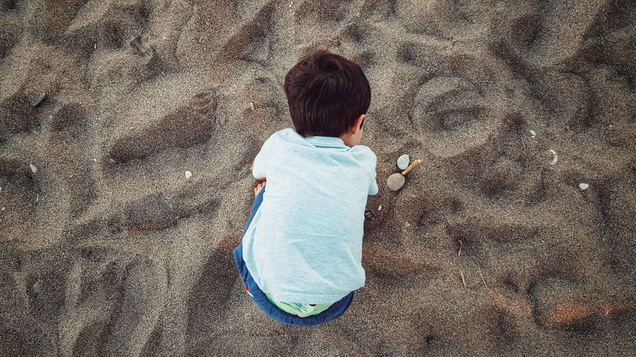 High Angle View Of Boy Bending On Sand At Beach
