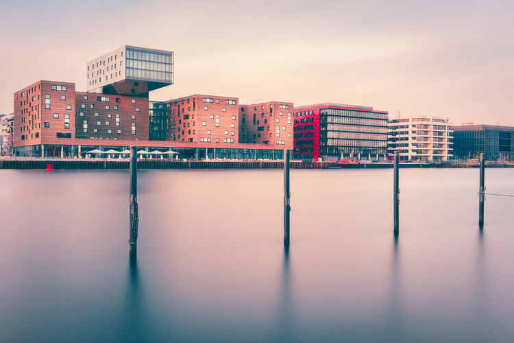 Buildings by spree river against sky during sunset
