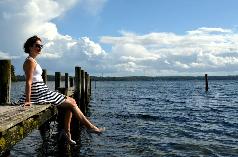 Baltic Sea Denmark Woman Beauty In Nature Cloud - Sky Clouds Day Full Length Leisure Activity Lifestyles Nature Non-urban Scene One Person Outdoors Real People Scenics - Nature Sea Sitting Sky Summer Tranquility Water Waterfront Wooden Post Young Adult