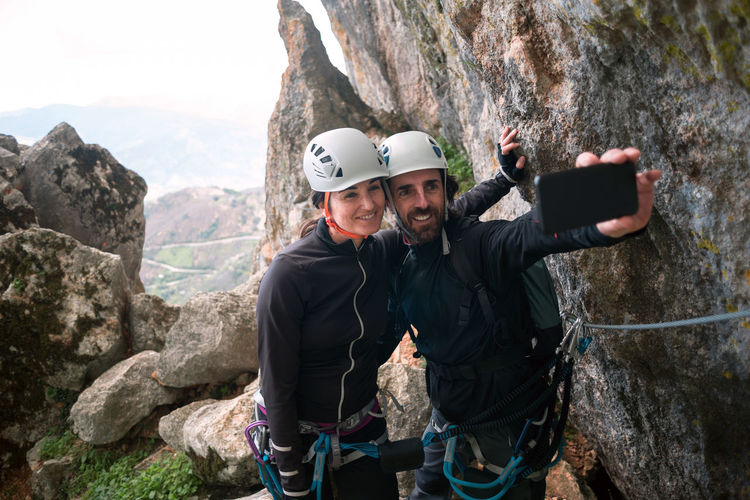 People enjoying on rocks against mountain range