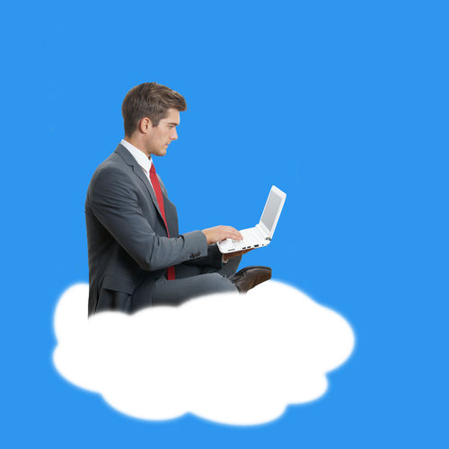 Digital Composite Image Of Young Man Using Laptop On Cloud Against Blue Background