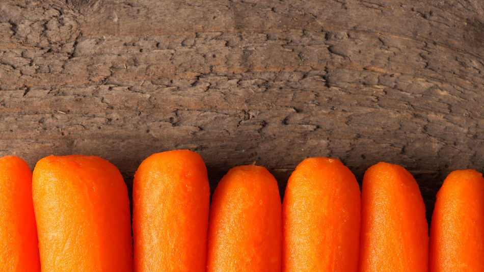 Baby carrots in a row Baby Carrots Carrots Close-up Day Food Food And Drink Freshness Header Healthy Eating Indoors  No People Orange Color Table Top View Vegetables Water Wooden