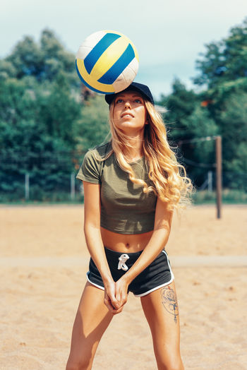 Young woman playing volleyball at sandy beach